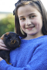 Girl Playing With Pet Guinea Pig Outdoors In Garden