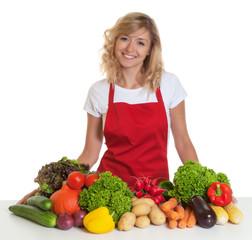 Lachende Hausfrau mit roter Schürze und frischem Gemüse