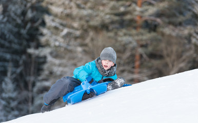 Boy turned around while he is sledging downhill
