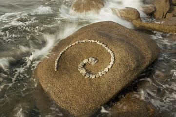 Esoterische Spirale aus Granitsteinen in der Brandung