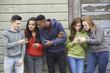 canvas print picture - Group Of Teenagers Sharing Text Message On Mobile Phones