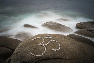 Symbol Om aus großen Kieselsteinen in der Brandung