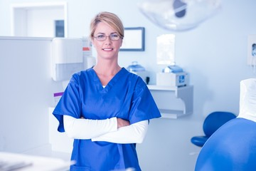 Portrait of a dentist smiling at camera with arms crossed