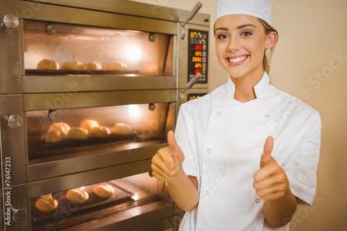 Baker smiling at camera beside oven