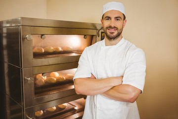 Baker smiling at camera beside oven