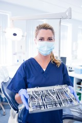 Dentist in blue scrubs offering tray of tools