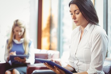 Thoughtful businesswomen using digital tablet