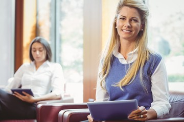 Smiling business colleagues with digital tablet