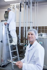 Scientist looking at camera with his colleague behind him