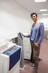 Smiling student standing next to the photocopier