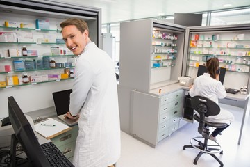 Happy pharmacist using the computer