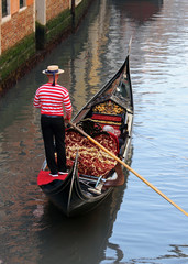 Venetian gondolier on his gondola on the Grand Canal
