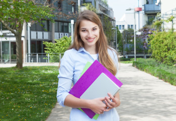 Studentin mit langen blonden Haaren an der Uni
