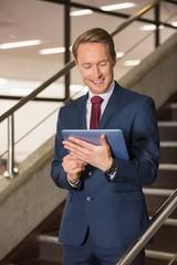 Handsome businessman standing on steps using tablet
