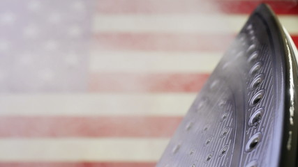 Iron releasing steam on a flag of the USA in 4K UHD video