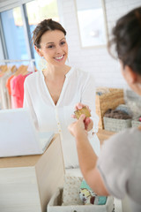Customer in clothing store giving credit card to saleswoman