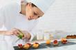Pastry-cook shreding lemon zest over cake bites - 76151075
