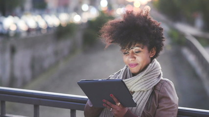 beautiful black curly hair african woman using tablet in town by