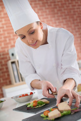 Young chef preparing plate of foie gras