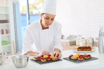 Pastry-cook preparing plate of cake bites