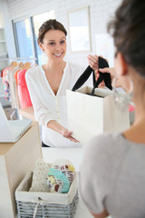 Seller woman in store giving purchase bag to client