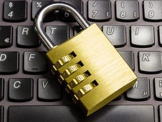 Locked combination padlock on keyboard symbolizing data security