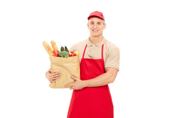 Male retail worker holding a grocery bag