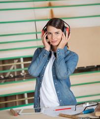 Female Carpenter Wearing Ear Protectors In Workshop