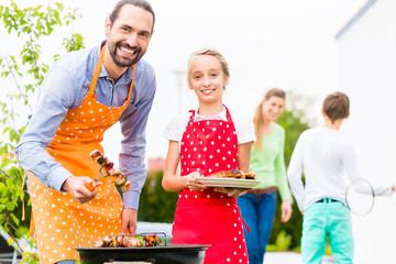 Vater und Tochter grillen zusammen auf Terrasse