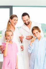 Familie beim Zähneputzen im Badezimmer