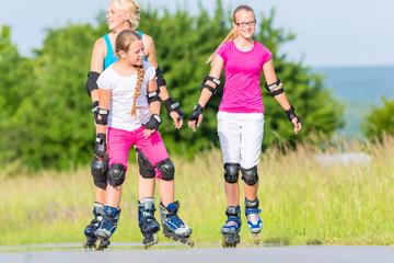 Familie beim skaten mit Inlinern auf Feldweg
