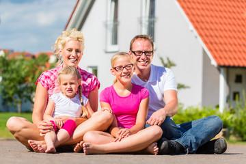Familie sitzt auf Straße vor Haus