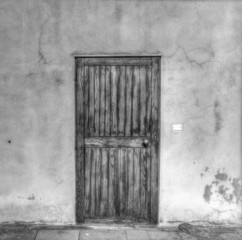 old wooden door in a grunge wall in black and white