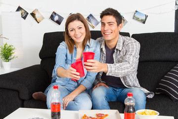 Couple toasting with red plastic cup