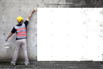worker painting the old wall in white