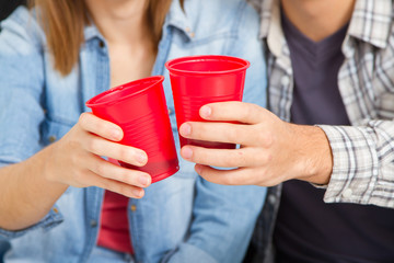 Closeup hands of friends toasting with red plastic cups