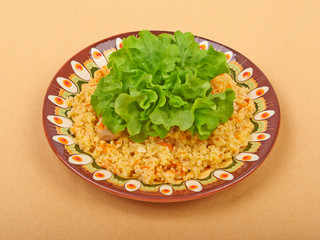 Pilaf dish, bulgur wheat with meat on a ceramic plate with lettu