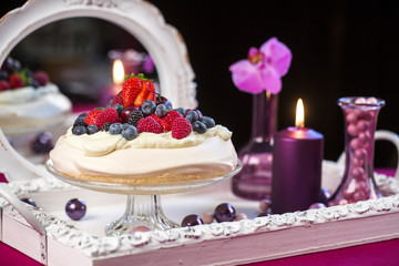 Pavlova cake, decorated with fresh strawberries and blueberries.