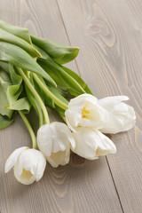 white tulips on rustic wood background