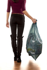 back view of woman holding garbage bag and leaves