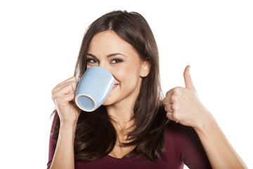 happy young woman drinking tea and showing thumbs up