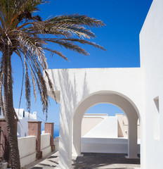 Traditional Greek architecture with white arch on blue sky.