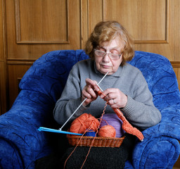 The old woman sits in an armchair and knits