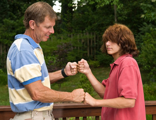 father and punk-haired son doing a fist bump