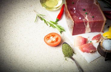 Jamon with herbs and spices, salt, olive oil and tomatoes on sto