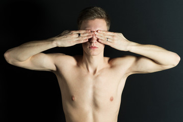 Attractive naked man hold hand cover his eyes on dark background