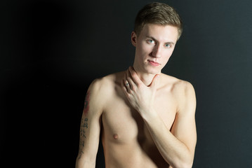 Young thin man, naked torso on black background