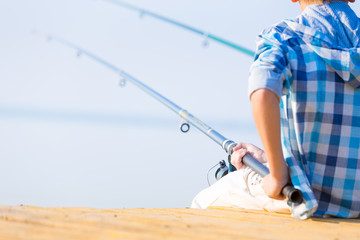 Close-up of hands of a boy with a fishing rod