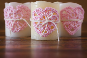 Three candles with handmade crochet pink heart for Saint Valenti