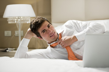 Relaxed businessman working on hotel bed